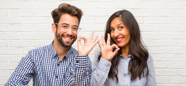 Jeune femme indienne et couple homme de race blanche gai et confiant faisant un geste ok