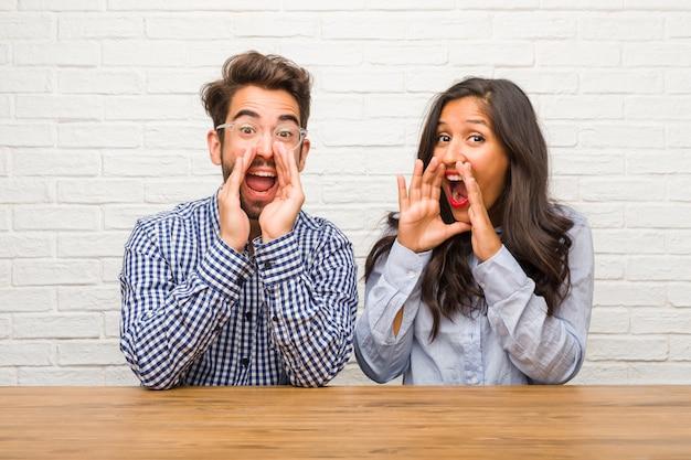 Jeune femme indienne et couple homme de race blanche hurlant heureux, surpris par une offre ou une promotion, béante, sautant et fière