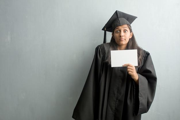 Jeune femme indienne diplômée contre un mur doutant et haussant les épaules