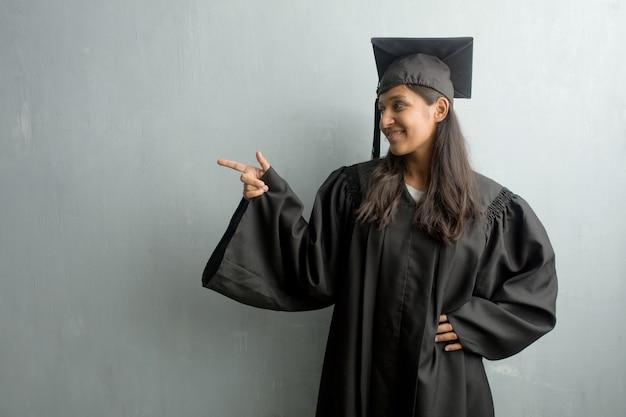 Jeune femme indienne diplômée contre un mur pointant vers le côté