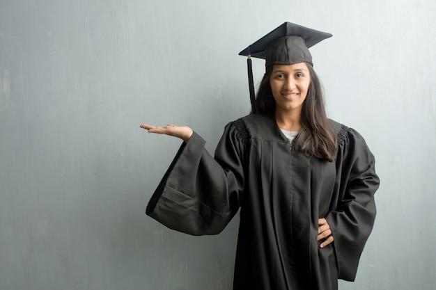 Jeune femme indienne diplômée contre un mur tenant quelque chose avec les mains, montrant un