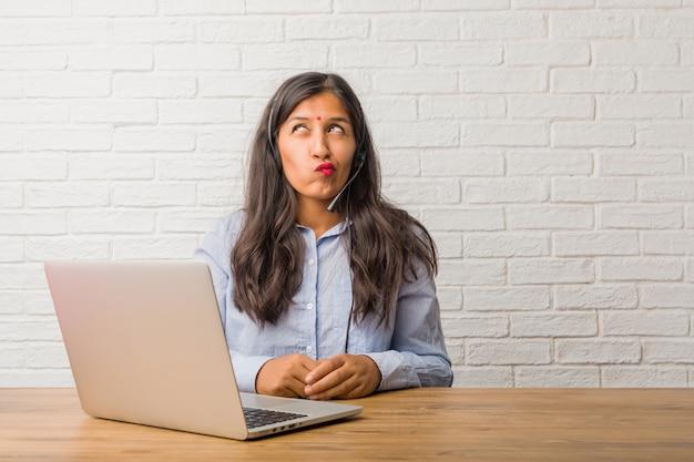 Jeune femme indienne douteuse et confuse, pensant à une idée ou inquiète.