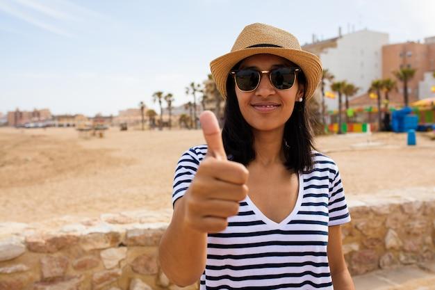 Jeune femme indienne fait un geste correct sur la plage