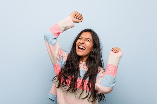 Jeune femme indienne fashion célébrant une journée spéciale, saute et lève les bras avec énergie.