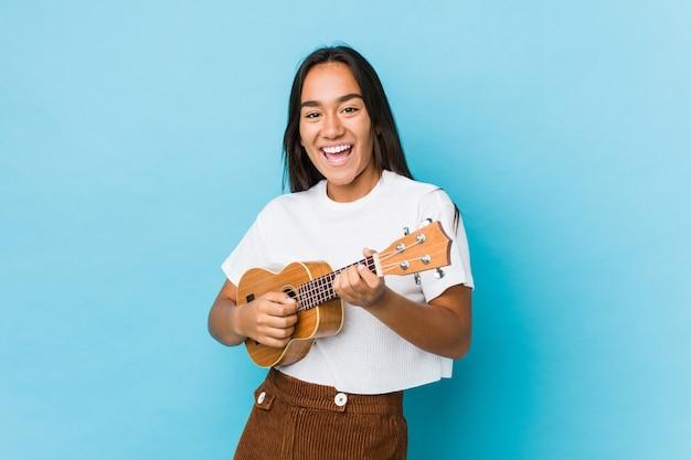 Jeune femme indienne heureuse jouant ukelele isolé