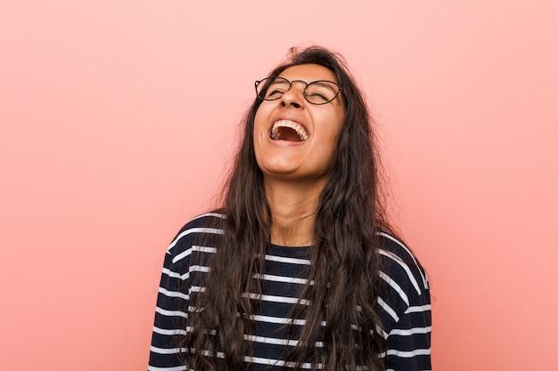Jeune femme indienne intellectuelle détendue et heureuse rire, cou tendu montrant les dents.