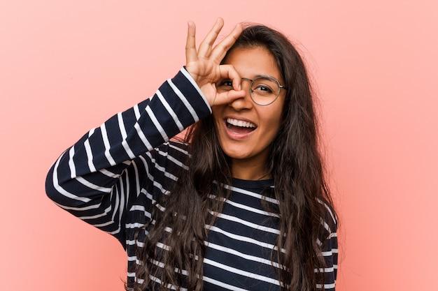 Jeune femme indienne intellectuelle excitée, gardant le geste correct sur le œil.
