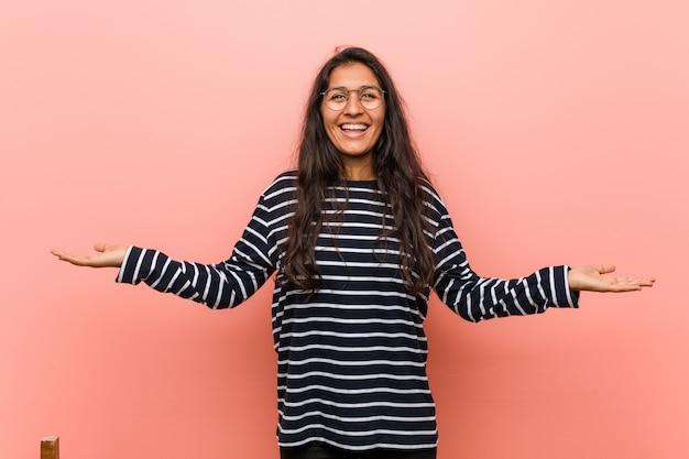 Jeune femme indienne intellectuelle fabrique une balance avec les bras, se sent heureuse et confiante.