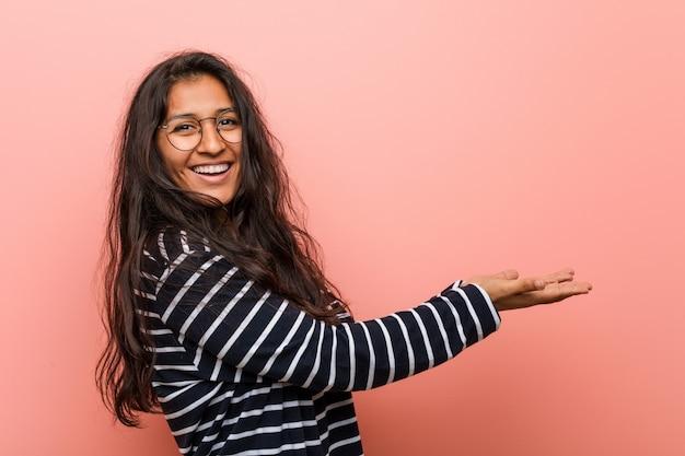 Jeune femme indienne intellectuelle tenant un espace de copie sur une paume.