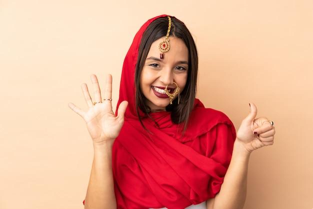 Jeune femme indienne isolée sur beige en comptant six avec les doigts