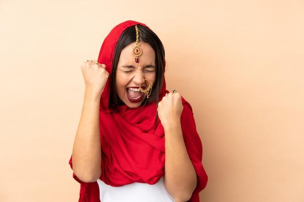 Jeune femme indienne isolée sur beige pour célébrer une victoire