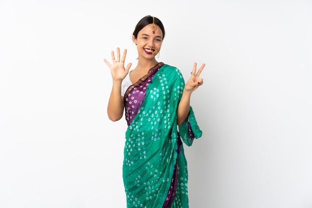 Jeune femme indienne isolée sur blanc en comptant sept avec les doigts