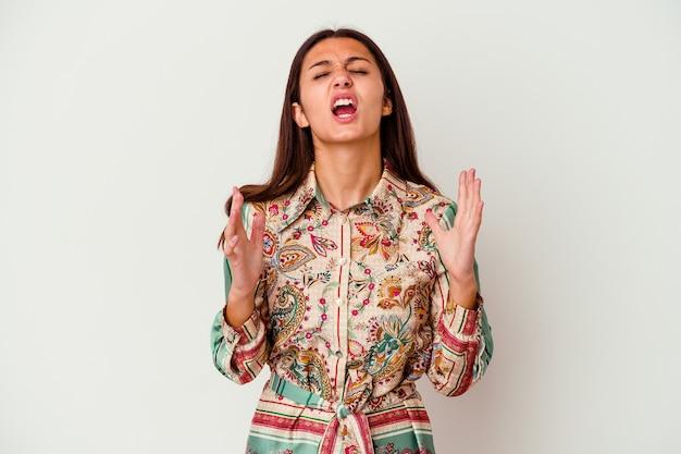 Jeune femme indienne isolée sur blanc criant vers le ciel, levant les yeux, frustrée.