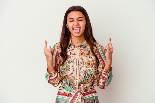 Jeune femme indienne isolée sur blanc montrant le geste de la roche avec les doigts