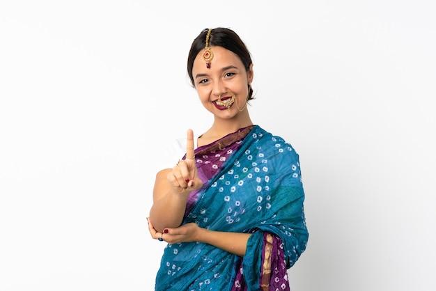 Jeune femme indienne isolée sur blanc montrant et soulevant un doigt