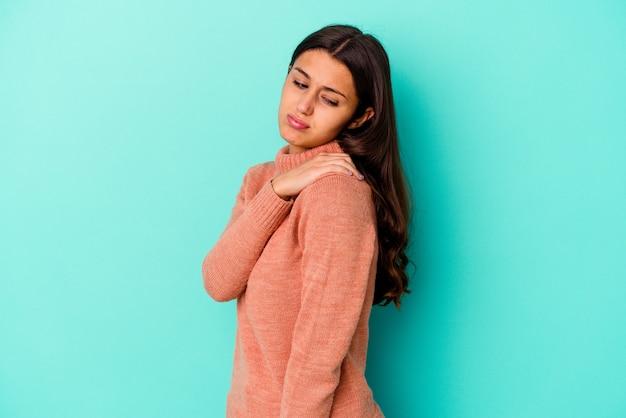 Jeune femme indienne isolée sur bleu ayant une douleur à l'épaule.