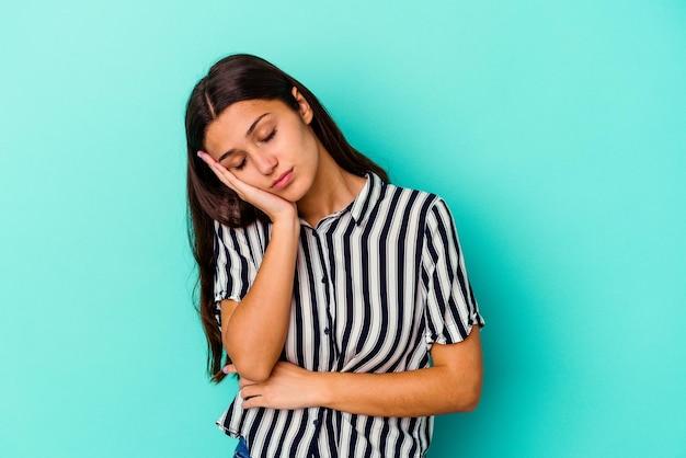 Jeune femme indienne isolée sur bleu qui s'ennuie, fatiguée et a besoin d'une journée de détente.