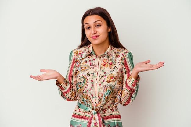 Jeune femme indienne isolée sur fond blanc doutant et haussant les épaules dans un geste de questionnement.