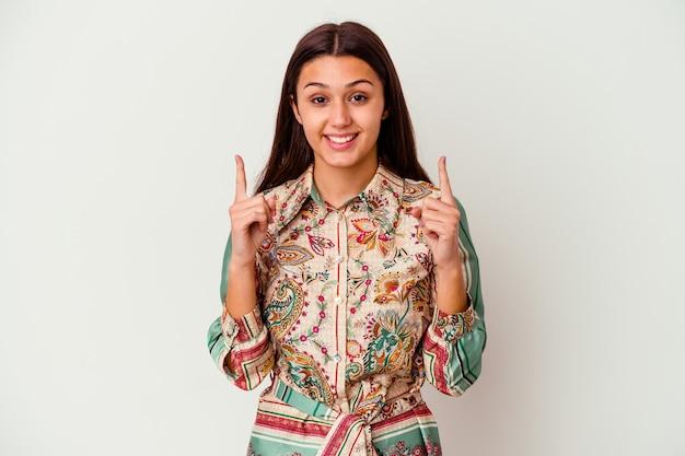 Jeune femme indienne isolée sur fond blanc indique avec les deux doigts avant montrant un espace vide.