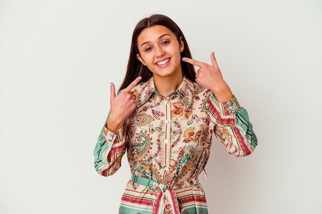 Jeune femme indienne isolée sur fond blanc sourit, pointant du doigt la bouche.