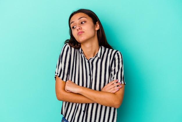 Jeune femme indienne isolée sur fond bleu fatigué d'une tâche répétitive.