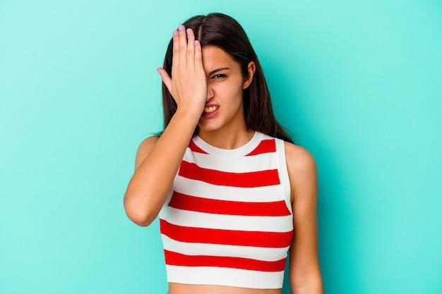 Jeune femme indienne isolée sur fond bleu oubliant quelque chose, giflant le front avec la paume et fermant les yeux.