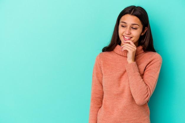 Jeune femme indienne isolée sur fond bleu pensée détendue sur quelque chose en regardant un espace de copie.