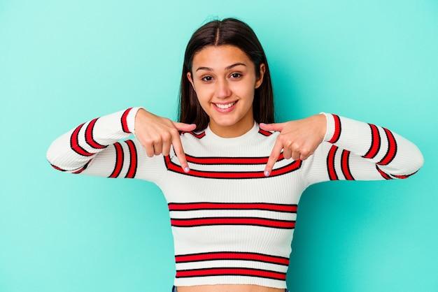 Jeune femme indienne isolée sur fond bleu pointe vers le bas avec les doigts, sentiment positif.