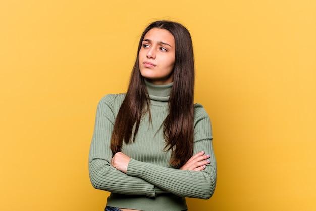 Jeune femme indienne isolée sur fond jaune rêvant d'atteindre les objectifs et les buts