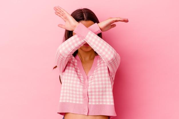 Jeune femme indienne isolée sur fond rose en gardant les deux bras croisés, concept de déni.