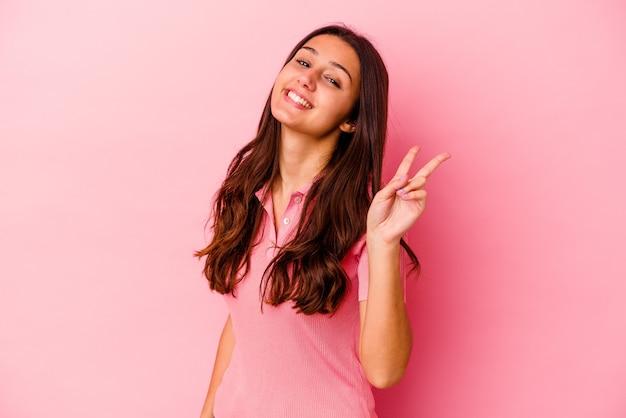 Jeune femme indienne isolée sur fond rose joyeux et insouciant montrant un symbole de paix avec les doigts.