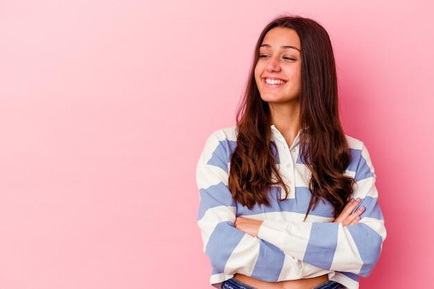 Jeune femme indienne isolée sur fond rose souriante confiante avec les bras croisés.