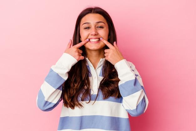 Jeune femme indienne isolée sur fond rose sourit, pointant du doigt la bouche.