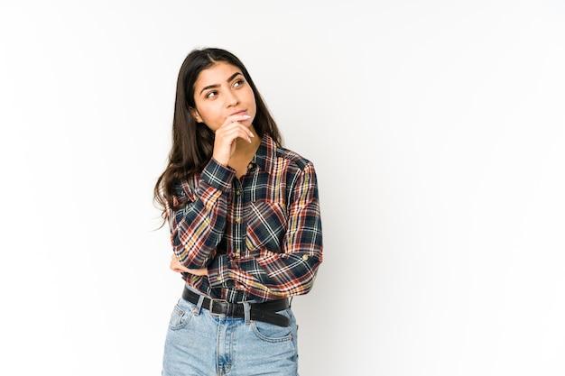 Jeune femme indienne isolée sur fond violet pensée détendue sur quelque chose en regardant un espace de copie.
