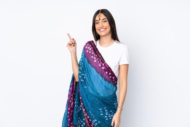 Jeune femme indienne isolée sur mur blanc montrant et levant un doigt en signe du meilleur
