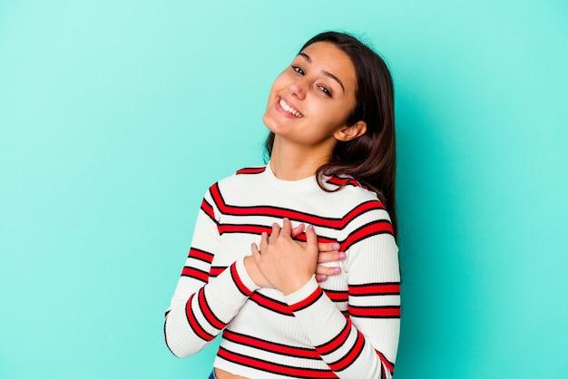 Jeune femme indienne isolée sur un mur bleu a une expression amicale, appuyant sur la paume de la main contre la poitrine. concept d'amour.
