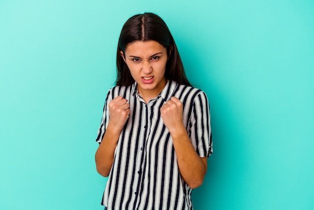 Jeune femme indienne isolée sur un mur bleu montrant le poing à la caméra, expression faciale agressive.