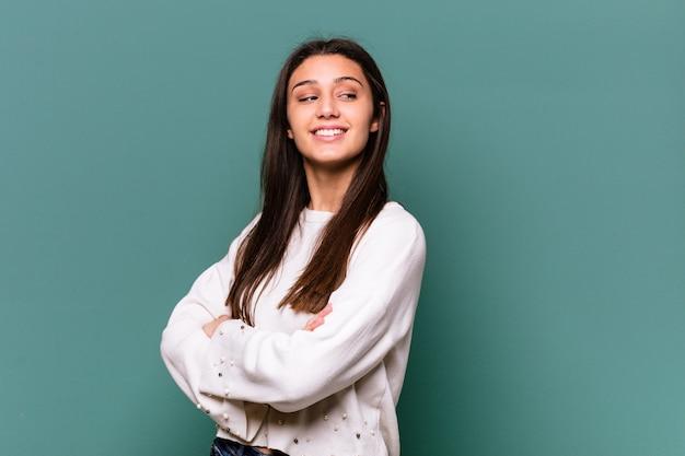 Jeune femme indienne isolée sur mur bleu en riant et en s'amusant