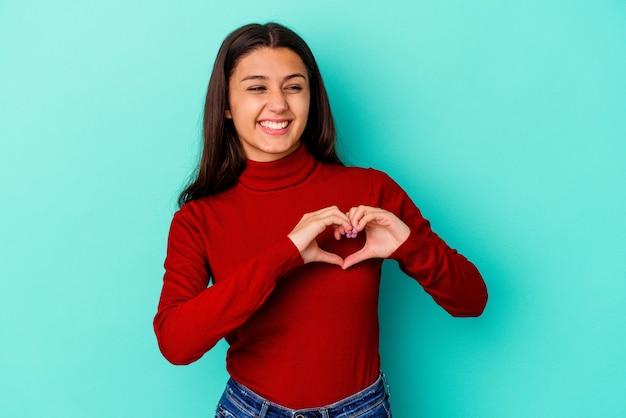 Jeune femme indienne isolée sur mur bleu souriant et montrant une forme de coeur avec les mains.