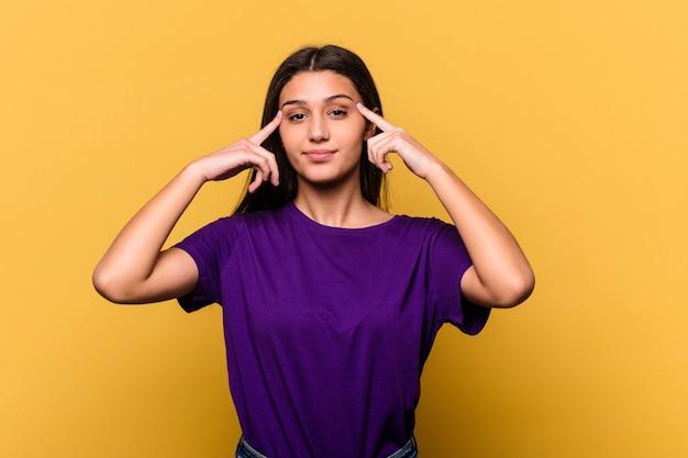 Jeune femme indienne isolée sur un mur jaune concentré sur une tâche, gardant l'index pointant la tête.