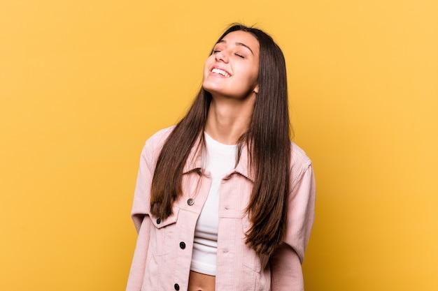 Jeune femme indienne isolée sur un mur jaune détendu et heureux de rire, cou tendu montrant les dents
