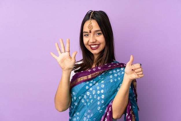 Jeune femme indienne isolée sur un mur violet comptant six avec les doigts