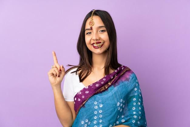 Jeune femme indienne isolée sur le mur violet montrant et levant un doigt en signe du meilleur