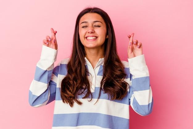 Jeune femme indienne isolée sur rose croisant les doigts pour avoir de la chance