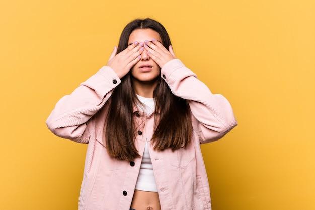 Jeune femme indienne sur jaune peur couvrant les yeux avec les mains.