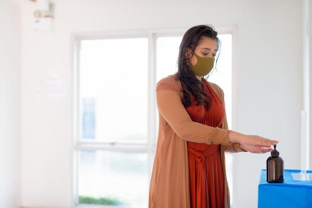 Jeune femme indienne avec masque à l'aide d'un désinfectant pour les mains comme bonne étiquette d'hygiène à l'intérieur