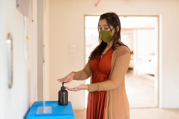 Jeune femme indienne avec masque à l'aide d'un désinfectant pour les mains à l'intérieur du bâtiment