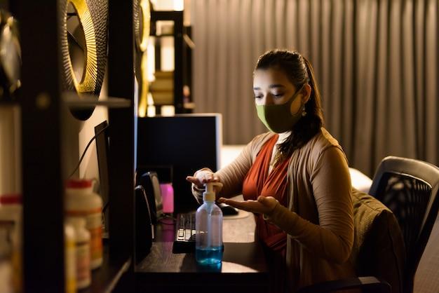 Jeune femme indienne avec masque à l'aide de désinfectant pour les mains tout en travaillant à domicile la nuit pendant la quarantaine