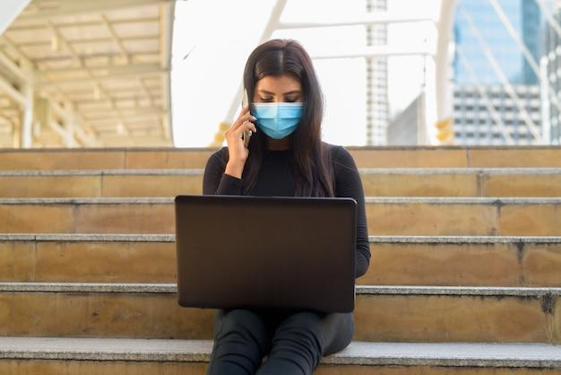 Jeune femme indienne avec masque à l'aide d'un ordinateur portable et parler au téléphone dans la ville