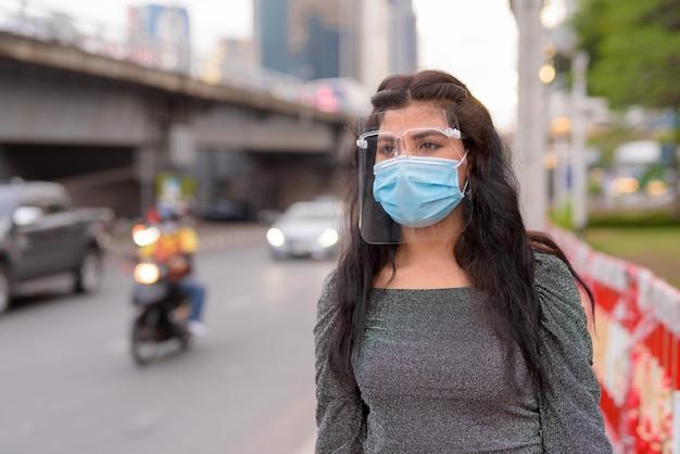Jeune femme indienne avec masque et écran facial pensant dans les rues de la ville